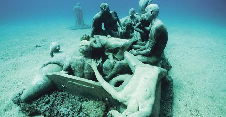 """Das """"Floß von Lampedusa"""" ist eines der Werke von Jason deCaires Taylor im Unterwassermuseum von Lanzarote. Als Vorbild diente ihm """"Das Floß der Medusa"""" von Théodore Géricault. Taylor setzte mit dieser Skulptur den vielen Migranten und Flüchtlingen, die im Atlantik ums Leben gekommen sind, ein Denkmal. Foto: Museo Atlántico"""