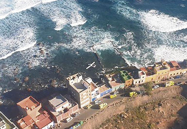 Das Kleinflugzeug landete nahe dem Naturschwimmbad von El Altillo und wurde dann durch die Brandung näher an das Ufer herangetragen. Foto: EFE