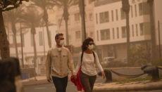 Zwei Spaziergänger im durch Wüstenstaub vernebelten Puerto del Rosario auf Fuerteventura am 23. Februar 2020. Vor dreieinhalb Wochen dienten die Atemschutzmasken noch zum Schutz vor den Sandpartikeln in der Luft. Foto: EFE