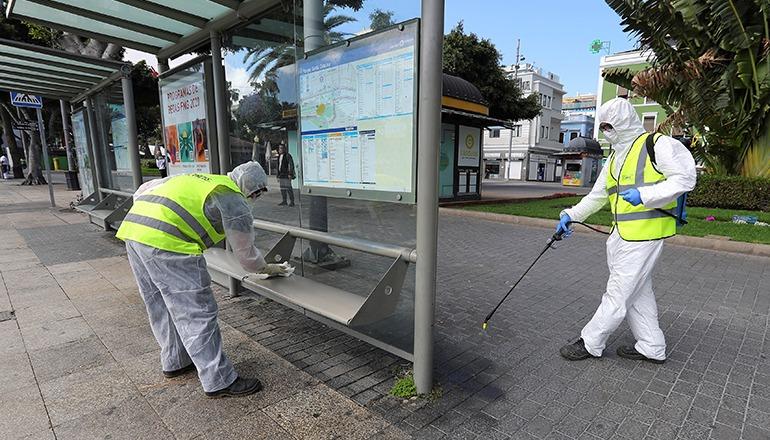 Zwei Mitarbeiter der Stadtreinigung desinfizieren das Stadtmobiliar und die Bushaltestellen im Parque Santa Catalina in Las Palmas. Foto: EFE