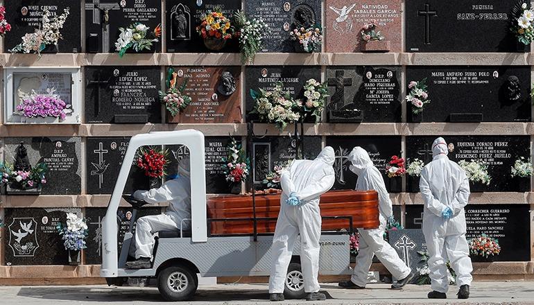 Friedhofspersonal beim Transport eines Sarges auf dem Friedhof Cabañal in Valencia. An der Beerdigung konnten maximal drei Familienangehörige teilnehmen. Foto: EFE
