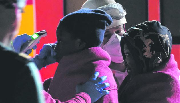 Ein Sanitäter prüft mit einem Infrarot-Thermometer, ob die Neuankömmlinge Fieber haben. Foto EFE