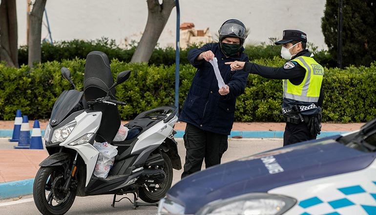 Ein Polizist in Murcia läßt sich die Arbeitsbescheinigung eines Verkehrsteilnehmers zeigen. Foto: EFE