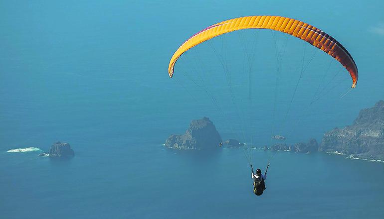 Ein Gleitschirmflieger über dem Tal von El Golfo mit Blick auf die Felsgruppe Roques de Salmor Foto: Rafa Avero