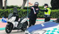 Ein Polizist kontrolliert einen Verkehrsteilnehmer während der Ausgangssperre. Foto: EFE