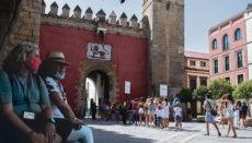 Touristen warten vor dem mittelalterliche Königspalast Alcázar von Sevilla auf Einlass. In der sommerlichen Hitze ist das Tragen von Masken besonders unangenehm, bleibt aber dennoch Pflicht. Foto: EFE