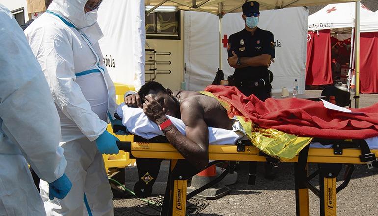 Einer der Kameraden des verstorbenen Migranten wird im Hafen von Arguineguín versorgt. Fotos: EFE