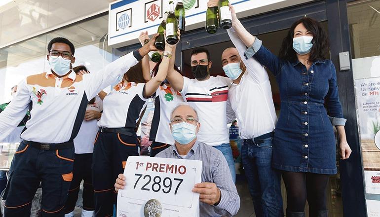 """Der Besitzer der Tankstelle des Glücks in Granadilla, José Miguel González, hält die Glückszahl des Hauptgewinns """"El Gordo"""" in die Kamera, während seine Angestellten anstoßen. Es ist das dritte Jahr in Folge, in dem an der Lotterieverkaufsstelle der Tankstelle Lose der Weihnachtslotterie verkauft wurden, auf die der Hauptgewinn fiel. Foto: efe"""