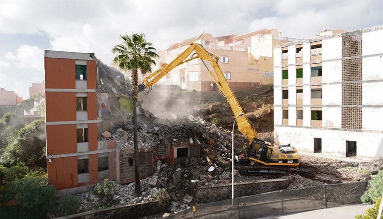 Ein riesiger Abbruchbagger wurde von Gran Canaria nach Teneriffa gebracht, um die fünfstöckigen Wohnhäuser abzureißen. Die Arbeiten gehen schneller voran als angenommen, und es wurden bereits fünf Gebäude abgerissen.