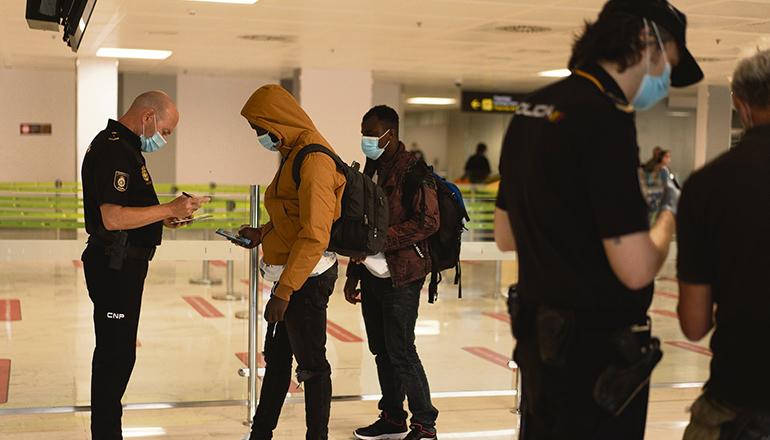Zwei Migranten werden vor Abflug am Südflughafen von der Nationalpolizei kontrolliert. Foto: EFE