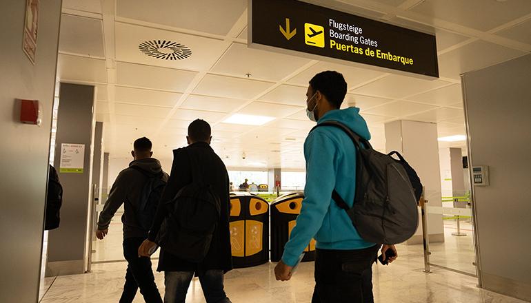 Drei Migranten auf dem Weg zum Flugzeug, das sie auf das spanische Festland bringen wird. Foto: EFE