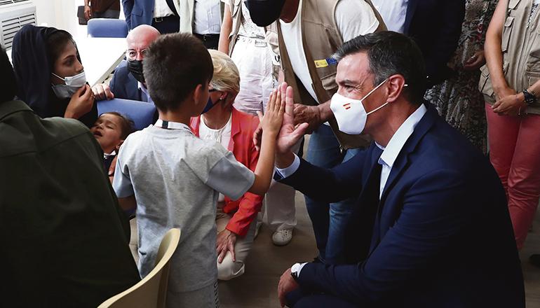Präsident Pedro Sánchez begrüßt ein afghanisches Flüchtlingskind im Aufnahmezentrum für Evakuierte in Torrejón de Ardoz. Foto: EFE