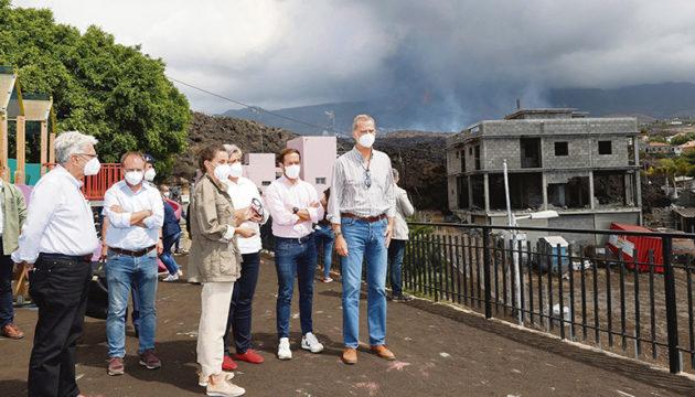 Beim Besuch eines der Orte, über die sich die Lavamasse ausbreitete, zeigten sich König Felipe und Königin Letizia tief betroffen vom Ausmaß der Katastrophe. Im Hintergrund ist zu sehen, wie der Vulkan weiter Lava ausspuckt. Foto: EFE