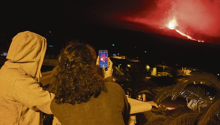 Beobachtung aus sicherem Abstand: Anwohner fotografieren das Naturschauspiel des Vulkans von Tajuya aus, in der Nacht vom 4. Oktober. Foto: EFE